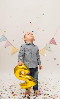 Kleine jongen in een shirt en broek staat en houdt een nummer twee van goudfolie vast
