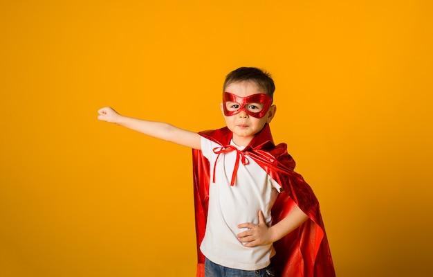 Kleine jongen in een superheldenkostuum op een gele ondergrond met ruimte voor tekst