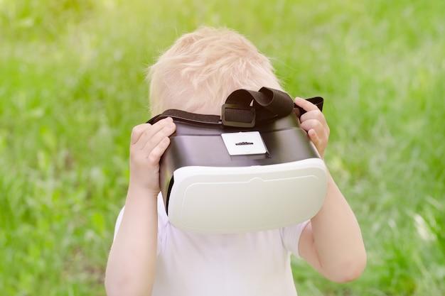 Kleine jongen in een virtual reality-helm op a van groen gras