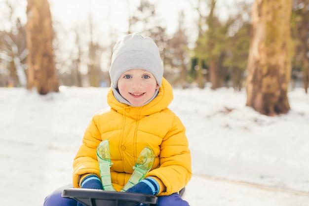 Kleine jongen in een wandeling in het park met zijn gezin in de winter, plezier maken en genieten van de sneeuw