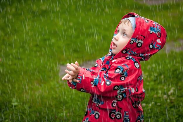 Kleine jongen in een waterdichte jas in tractoren vangen de regen. kind plezier buitenshuis in zomer douche