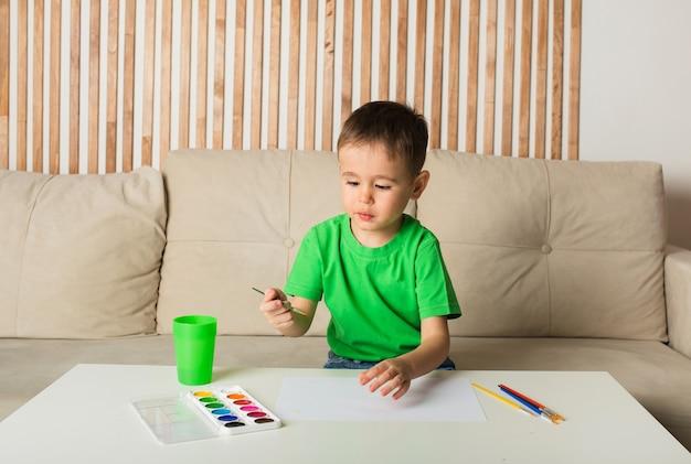 Kleine jongen in een wit t-shirt tekent met een penseel en schildert op papier aan een tafel in de kamer