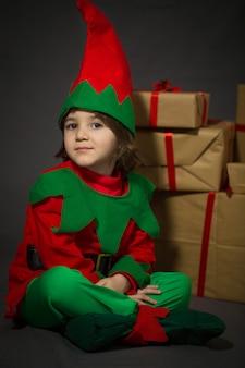 Kleine jongen in elf jurk zitten in de buurt van een geschenkdozen