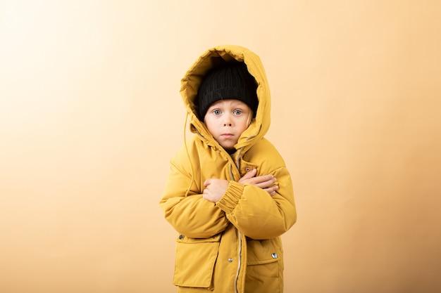 Kleine jongen in gele jas, trui en hoed op geel
