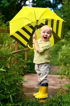 Kleine jongen in gele laarzen onder een gele paraplu lacht