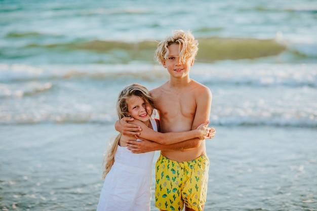 Kleine jongen in gele zwembroek en meisje in witte zomer overall poseren aan de zeekust.