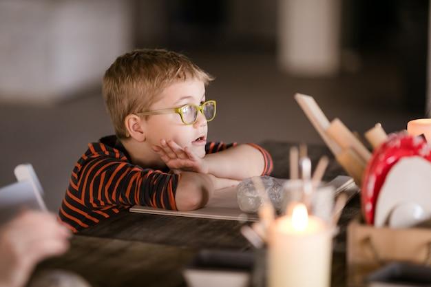 Kleine jongen in grote glazen beeldhouwt met interesse uit klei