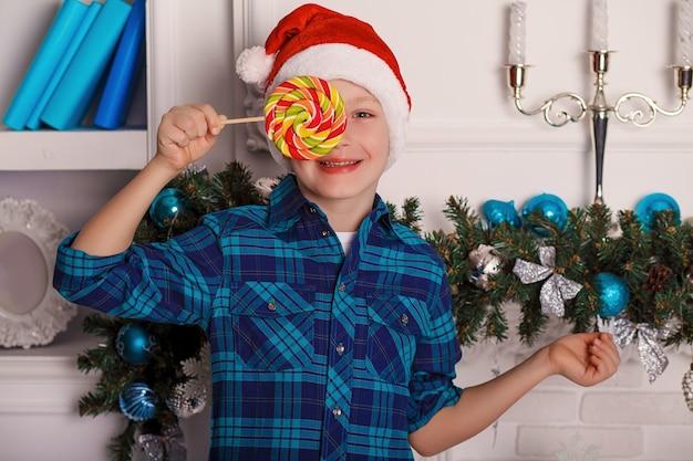 Kleine jongen in kerstman hoed houdt een grote smakelijke lolly in zijn hand in de kamer met kerstversiering