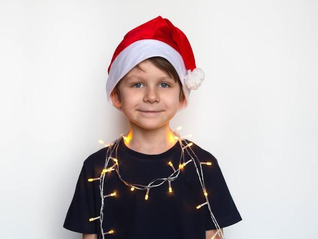 Kleine jongen in kerstmuts met een krans om zijn nek, kerst concept