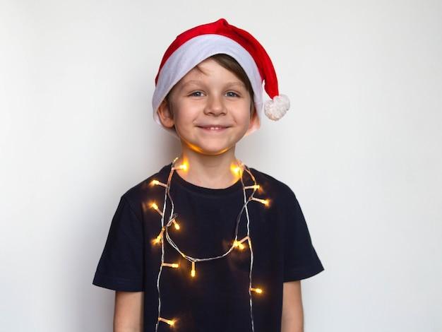 Kleine jongen in kerstmuts met een krans om zijn nek