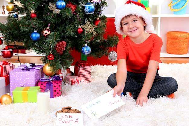 Kleine jongen in kerstmuts met melk, koekjes en brief voor de kerstman