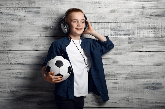 Kleine jongen in koptelefoon houdt bal in studio. kinderen en gadgets, kind geïsoleerd op houten achtergrond, emotie van het kind, fotosessie van de schooljongen