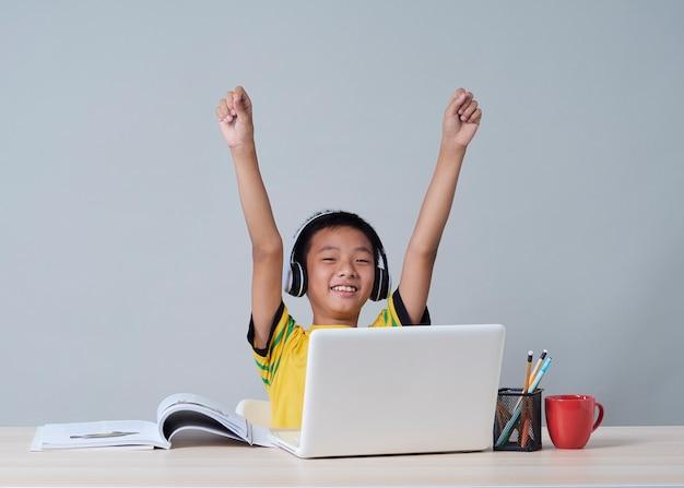 Kleine jongen in koptelefoon studeren online met behulp van laptop