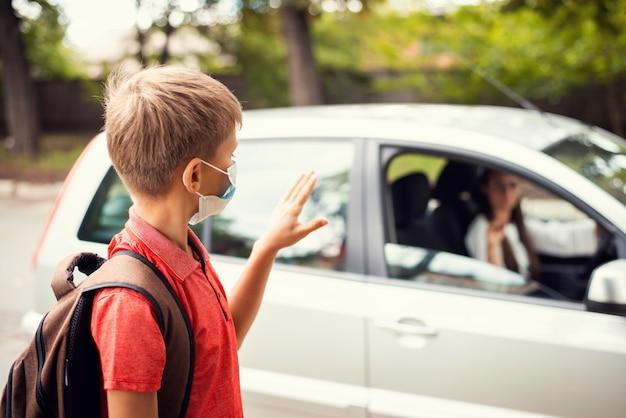 Kleine jongen in medisch masker uitzwaaien naar zijn moeder in de auto voor school