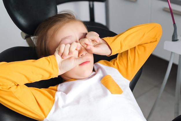 Kleine jongen in medische stoel met gesloten ogen bang kind op bezoek bij specialist in tandheelkundige kliniek