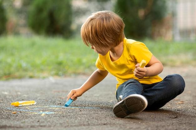 Kleine jongen in park tekenen