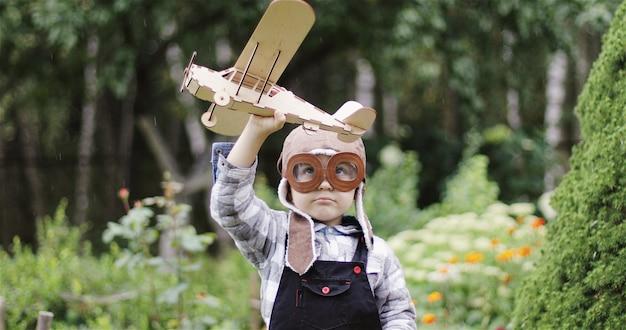 Kleine jongen in pilotenhoed spelen met houten vliegtuig gelukkig kind met een speelgoedvliegtuig