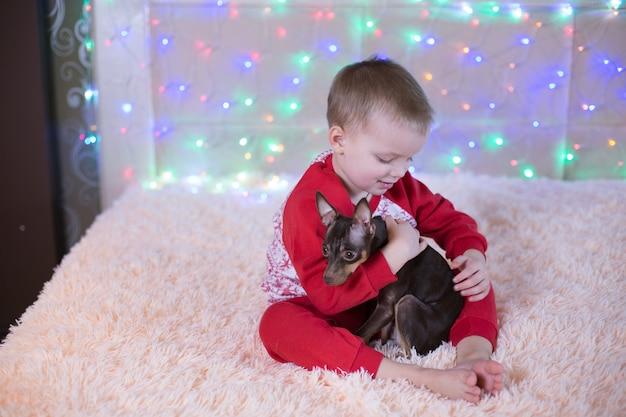 Kleine jongen in rode pyjama's spelen met een hond op kerstavond