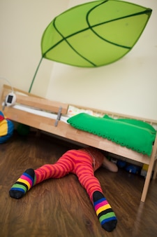 Kleine jongen in rood gestreepte broek en sokken kijkt onder het bed op zoek naar speelgoed