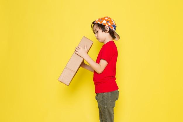 Kleine jongen in rood t-shirt en kleurrijke pet houden doos op de gele muur