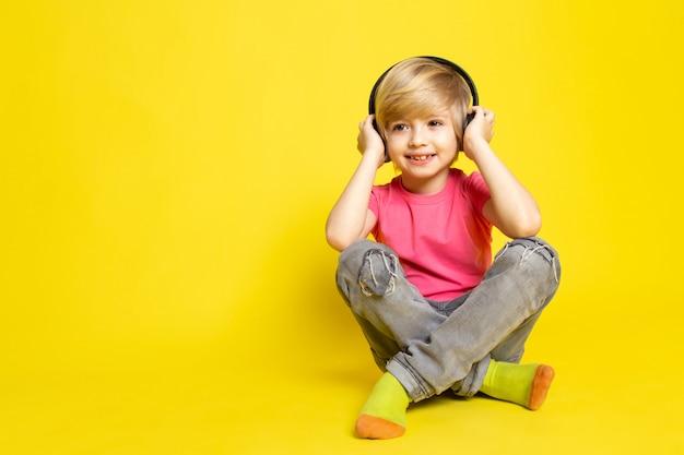 Kleine jongen in roze t-shirt en zwarte koptelefoon luisteren naar muziek
