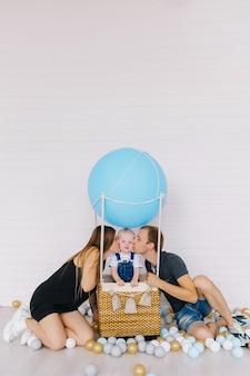 Kleine jongen in spijkerbroek op blauwe ballon op wit met zijn familie. ouders kussen hun zoon.