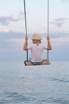 Kleine jongen in strooien hoed rijden op schommel over het water. zomervakantie.