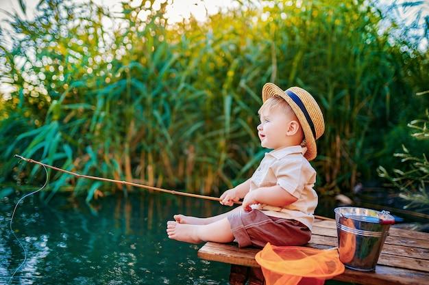 Kleine jongen in strooien hoed zittend op de rand van een houten dok en vissen in meer bij zonsondergang.