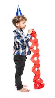 Kleine jongen in verjaardag hoed met papieren slinger van rode harten