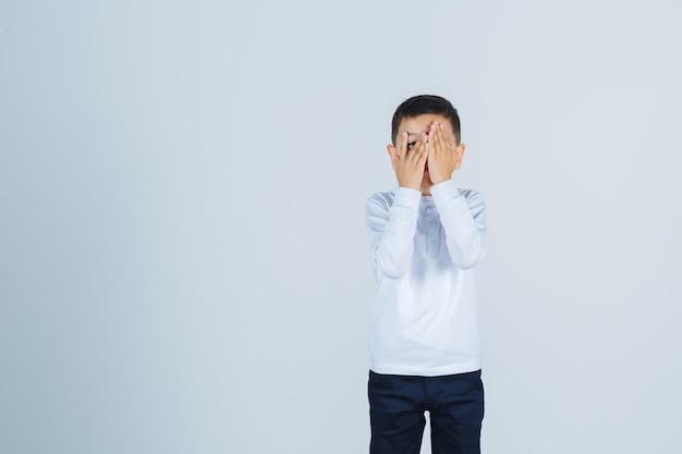 Kleine jongen in wit overhemd, broek die door vingers kijkt en bang kijkt, vooraanzicht.
