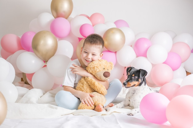 Kleine jongen in witte ballonnen met hem hond