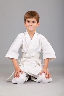 Kleine jongen in witte kimono karate beoefenen