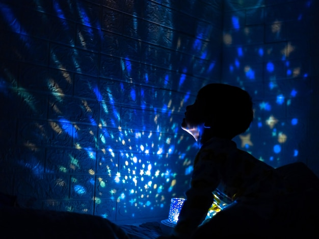 Kleine jongen in zijn kamer met nachtlicht dat sterren op het plafond van de kamer projecteert. kinderen lezen voor het slapengaan.