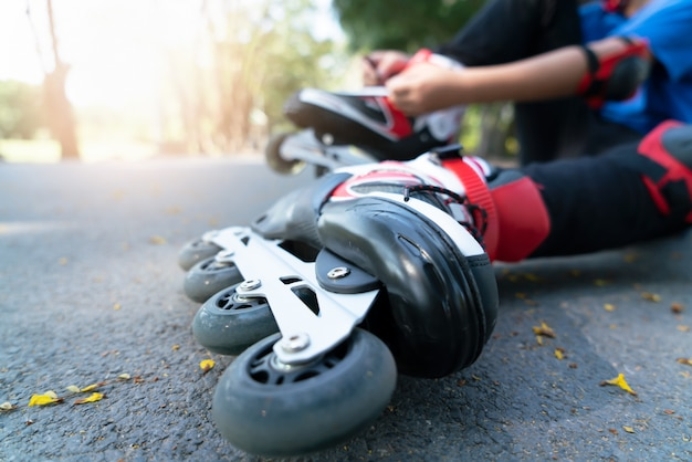 Kleine jongen instelling van kant op zwarte rolschaatsen