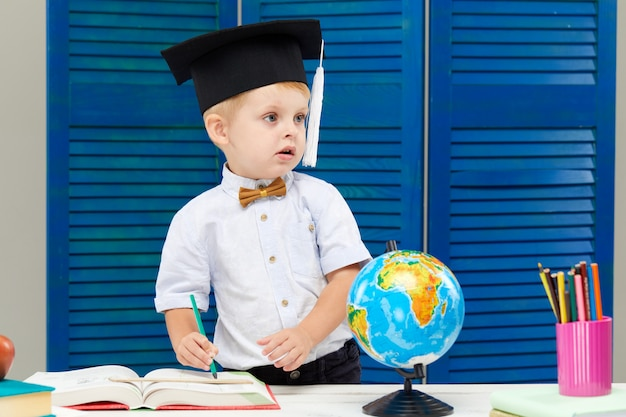 Kleine jongen is studeren terwijl het dragen van een afstuderen cap