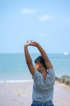 Kleine jongen jongen staan op strand en strekken zichzelf