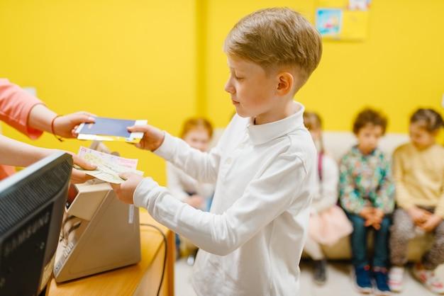 Kleine jongen kaartje in de speelkamer kopen.