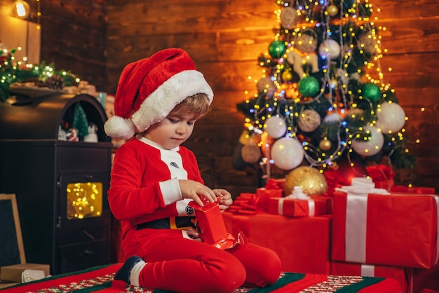 Kleine jongen kerstboom versieren en geschenken openen nieuwjaar kersttijd elf kind winter winkelen ...