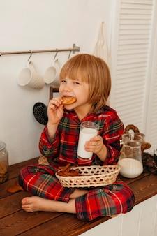 Kleine jongen kerstkoekjes eten en consumptiemelk