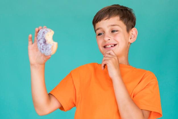 Kleine jongen kijkt naar een donut