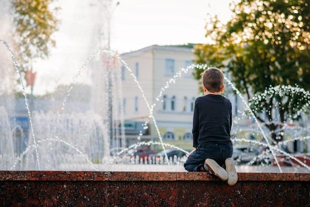 Kleine jongen kijkt naar een fontein op zonnige avond