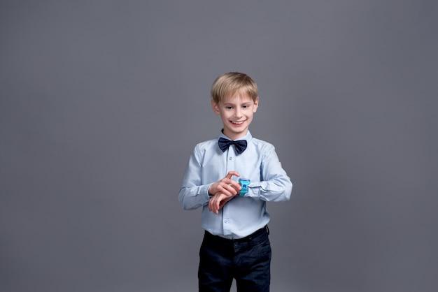 Kleine jongen kijkt naar het horloge en poseren op een grijze