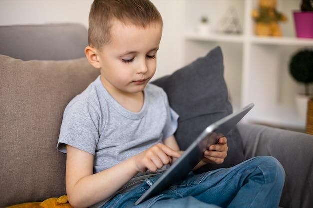 Kleine jongen kijkt naar zijn tablet