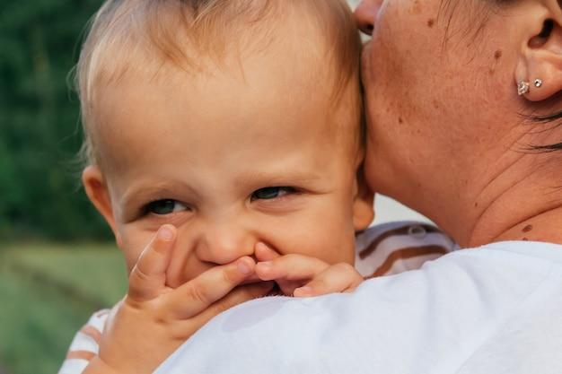 Kleine jongen kijkt over de schouder van zijn moeder