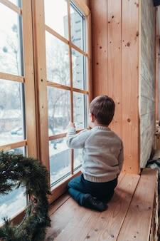 Kleine jongen kijkt uit het raam met zijn hand over het glas
