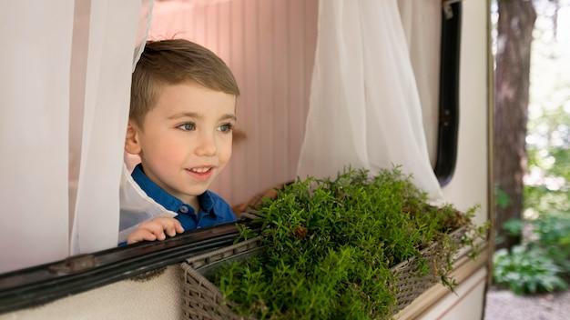 Kleine jongen kijkt uit het raam van zijn caravan