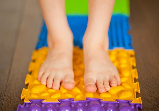 Kleine jongen kind lopen op een orthopedische massagemat. behandeling en preventie van platvoeten bij kinderen.