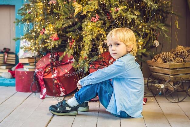 Kleine jongen klaar voor de vakantie in de buurt van de kerstboom