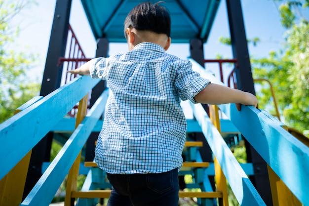 Kleine jongen klimmen op trap om schuif te spelen
