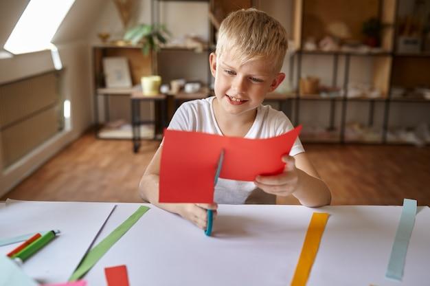 Kleine jongen knipt gekleurd papier, kinderen in werkplaats